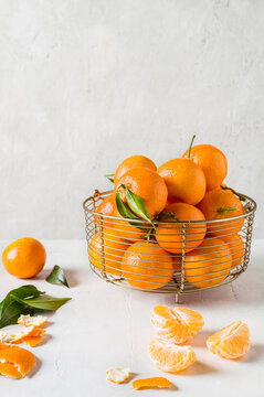 Tangerines, oranges, mandarins, clementines,  with leaves in fruit bowl. Front  view. Space for text
