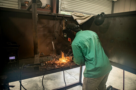A man welds two pieces of metal together in a shop with an arc welder.