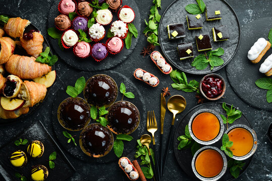 Set of sweets and desserts for coffee and tea on a black stone background. Top view. Rustic style.