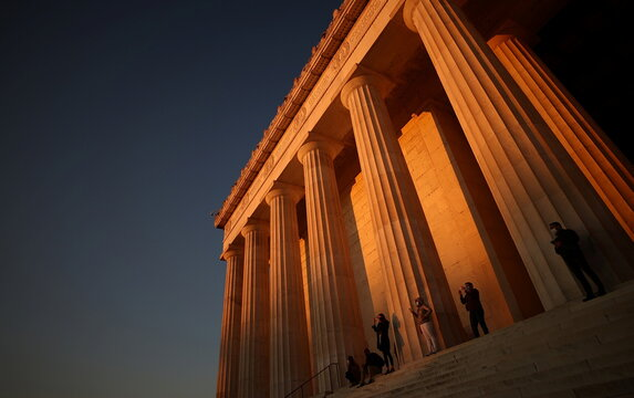 People watch the sun rise from the steps of the Lincoln Memorial on the National Mall in Washington
