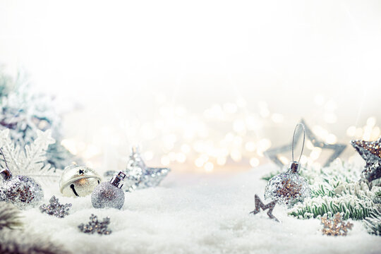 Christmas silver decorations on snow with fir tree branches and christmas lights. Winter Decoration Background