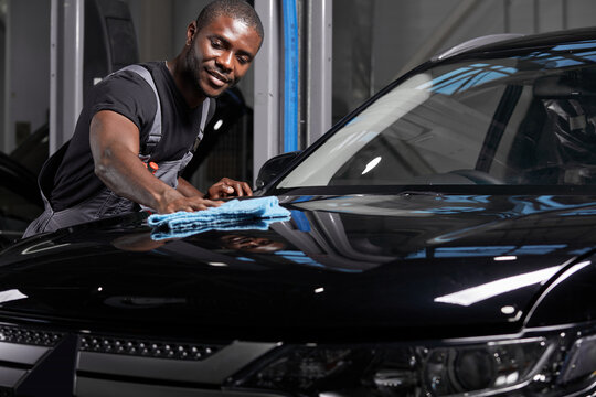 young adult afro american man cleaning car with microfiber cloth, car detailing or valeting concept