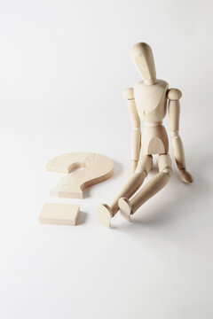 wooden mannequin with question mark