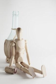 wooden mannequin sitting next to empty bottle