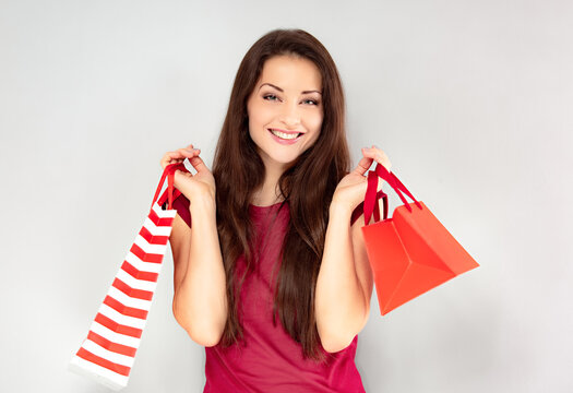 Excited happy woman in red dress looking happy and holding gift red packages with smiling on blue light background. Happy holidays.