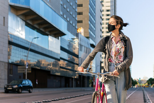 girl with a bike wearing protective mask at city