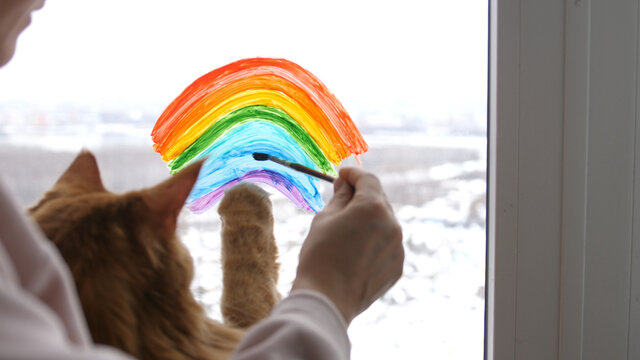 Young woman sitting with cat and painting rainbow on window during Covid-19 quarantine at home in winter. Stay at home Social media campaign for coronavirus prevention.