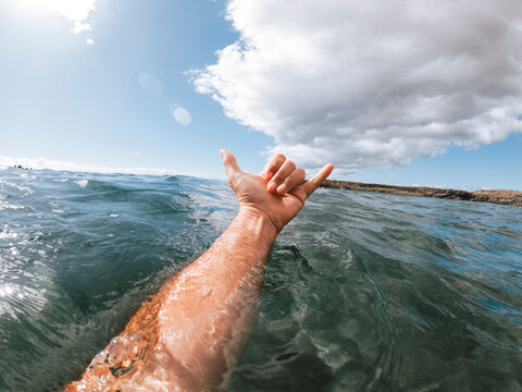 Man hands in surf sign hallo out of the blue ocean water with coast and nice sky in background - concept of people and summer holiday vacation