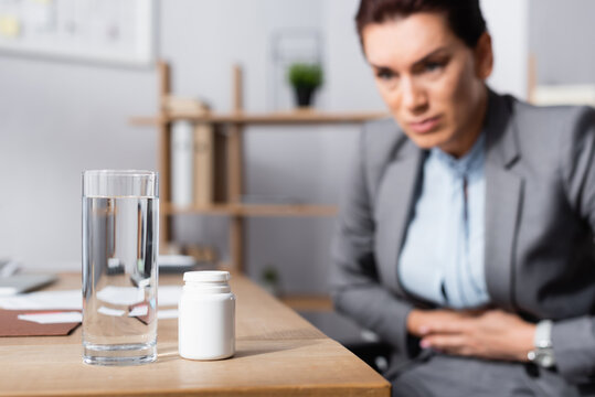Glass of water and medication on desk with blurred businesswoman with stomachache on background