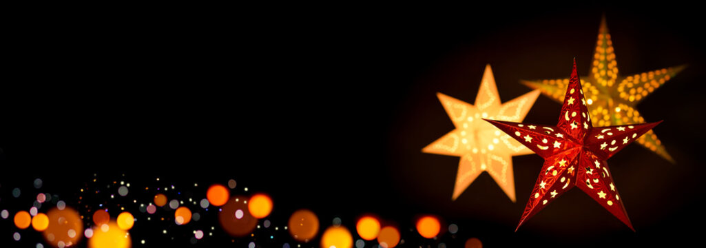 Shining red and gold Christmas star lanterns framing a simple, extra wide black background as copy space