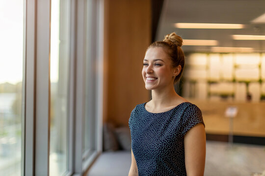 Smiling businesswoman standing in office and looking out of window