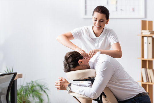 Happy masseuse doing neck massage for businessman in office on blurred background