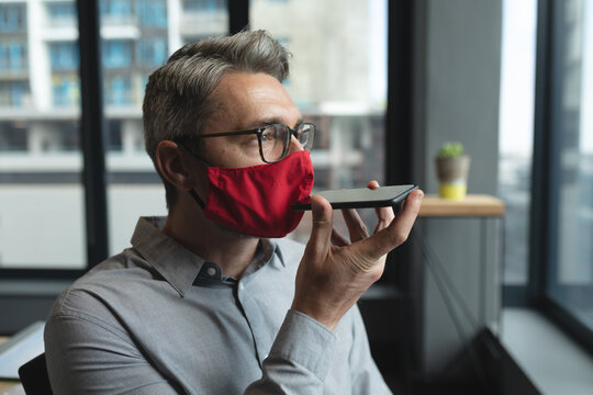 Caucasian man wearing face mask talking on smartphone at modern office