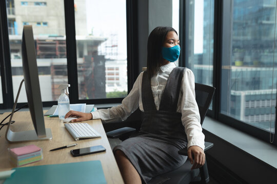 Asian woman wearing face mask sitting on her desk looking out of window at modern office