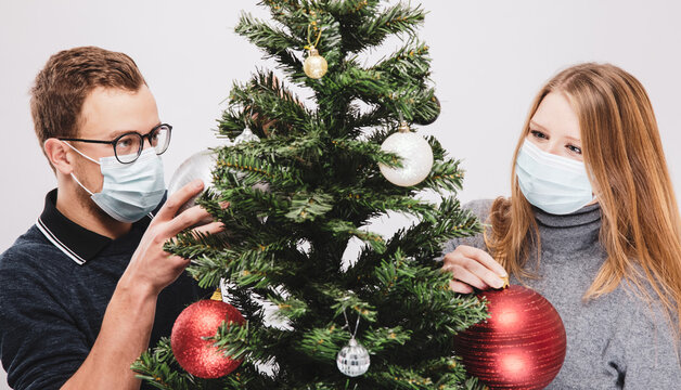 Couple decorating the Christmas tree wearing covid-19 face mask