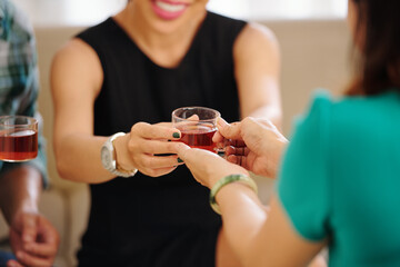 Close-up image of woman giving cup of tasty hot black tea to smiling party guest