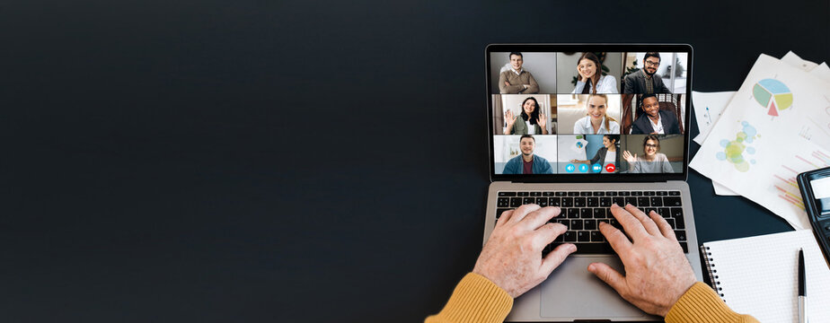 Top view of laptop screen with video conference participants and mature man's hands on keyboard, laptop stands on a black desktop. Copy space