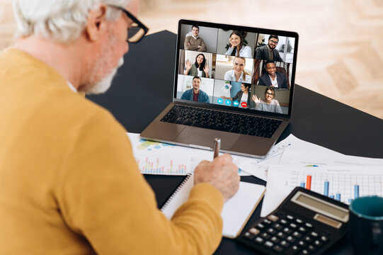 Caucasian senior man is sitting at the work desk using a laptop for remote online studying ,he writes information, and on a laptop screen are a teacher and other participants of the video conference