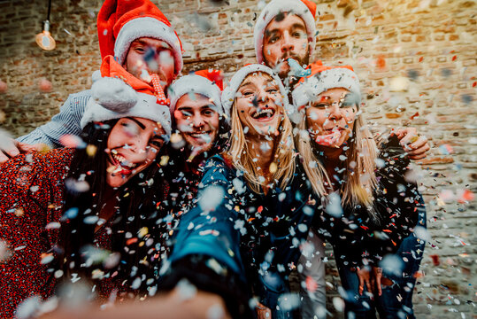 Group friends with santa hat celebrating Christmas time taking a selfie - Winter holiday concept with young people having fun at new year eve