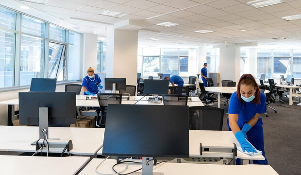 Professional cleaners with the masks on their faces clean and disinfect an empty office space