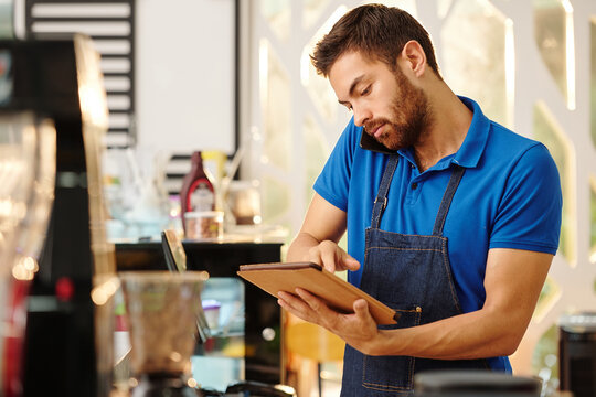 Cafe owner talking on phone with customer and taking notes on tablet computer