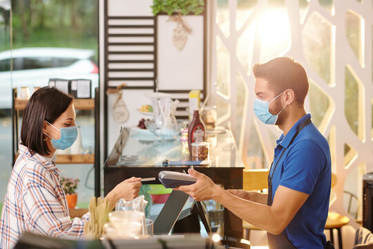 Pretty young woman in medical mask paying for order in cafe with credit card