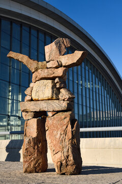 Inukshuk red stone statue with outstretched welcoming arms at Pearson International Airport Terminal 1 Toronto Canada in morning sunrise Toronto, Canada - June 7, 2019