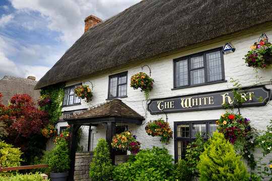 Front garden of the White Hart Pub and Innwith whitewashed stone building and thatched roof  in Wroughton, Wiltshire, England - June 9, 2019