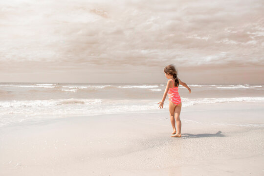 Little girl on a beach with muted color in the ocean and sky