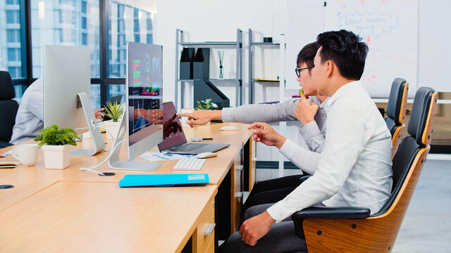 Asian businessman discuss together in office, coworker work on laptop computer. Corporate business, financial consult, partnership teamwork, or information technology concept