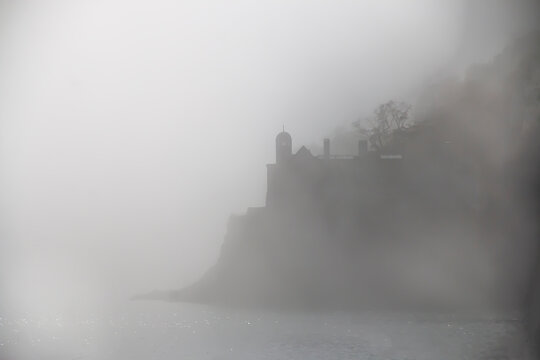 House on a cliff by the ocean on a foggy day