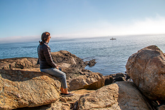Woman sitting on rocks looking out to sea