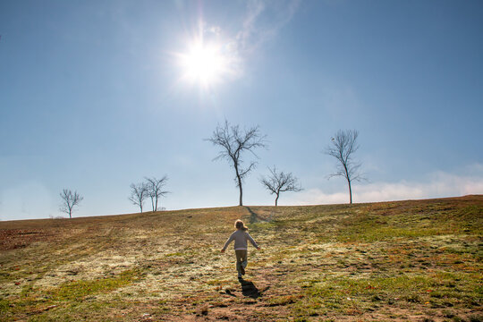 Girl running up a hill toward the trees