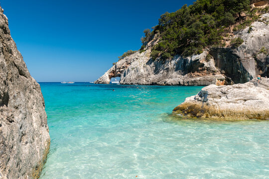 The coastline in Cala Goloritze, famous beach in the Orosei gulf (Ogliastra, Sardinia, Italy) with a natural arch in the background