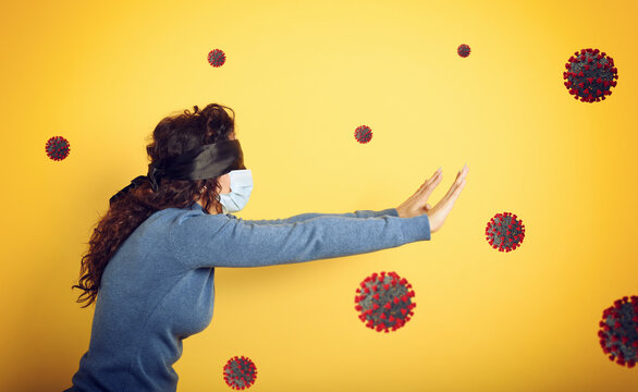 Woman with mask and blindfold. concept of uncertainty. yellow background