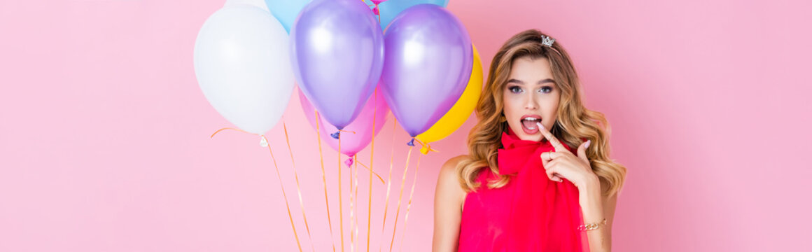 elegant surprised woman in crown with balloons on pink background, banner