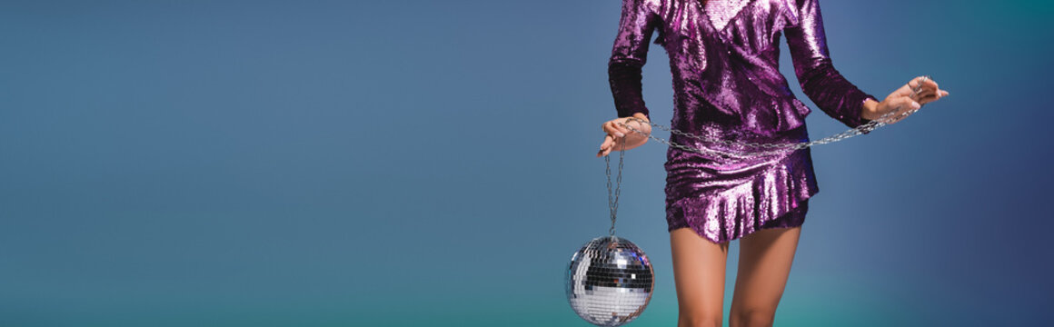 cropped view of elegant woman in sequin dress with disco ball on blue background, banner