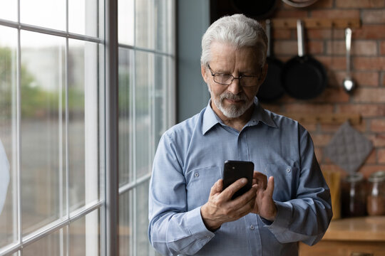 Close up satisfied mature man wearing glasses using phone, standing near window at home, cheerful senior male looking at smartphone screen, browsing apps, shopping or chatting with relatives online