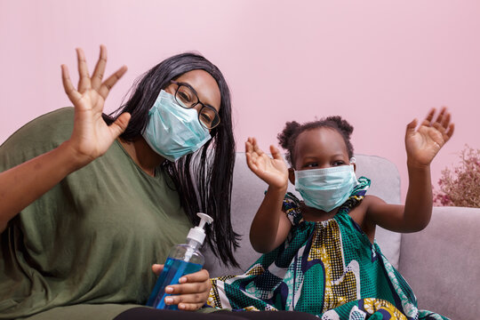 African Americans' mother and daughter wearing a mask are washing their hands with alcohol to protect them from germs and COVIC 19 while staying at home. black people or African Americans
