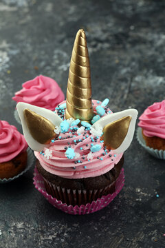 Unicorn cupcakes decorated with colorful buttercream icing and sprinkles on table
