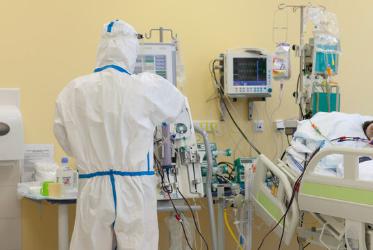 Male nurse with protective coverall clothing in intensive care unit in hospital, where are  treated patients with pneumonia caused by coronavirus covid 19.