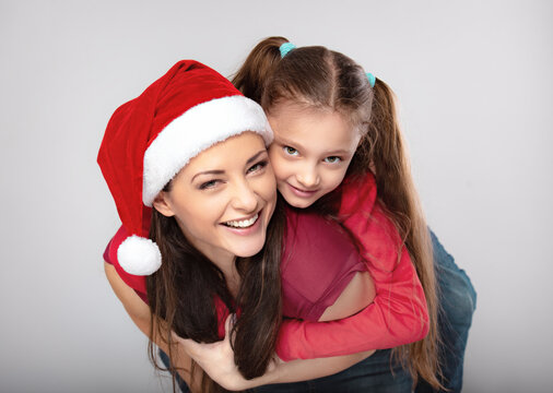 Happy laughing excited mother with open mouth hugging with love her cute joying daughter in santa clause hat and holding on the back. Portrait