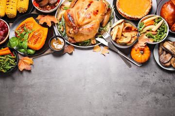 Traditional Thanksgiving day feast with delicious cooked turkey and other seasonal dishes served on...