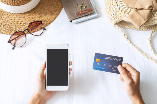 Hand holding credit card while using mobile phone with travel item on bed. Holiday, technology and lifestyle, cashless society concept.