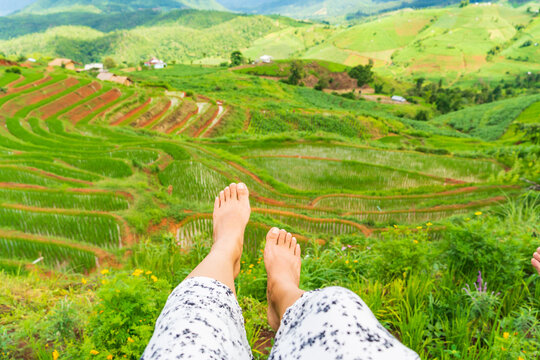 Woman relaxing at rice field terrace.