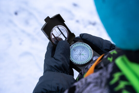A boy in mittens in the winter forest holds a compass in his hands. Boy trying to navigate in the forest using a compass