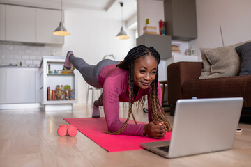 Young african america woman at home doing exercise in front of open laptop, repeating instructions...