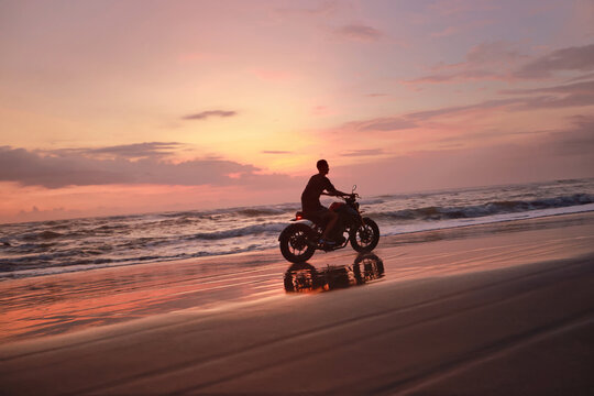 Man And Motorcycle On Ocean Beach At Beautiful Tropical Sunset. Biker's Silhouette On Motorbike On Sandy Coast Near Sea In Bali, Indonesia.