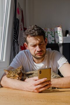 A young man with a cat in his arms looks into the phone at an incoming sms.A man hugs a sleeping cat and surfs on the phone.