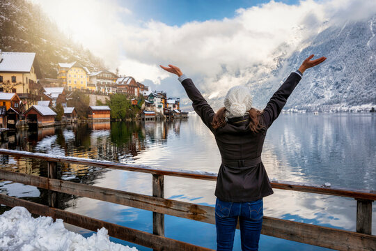 A happy traveler woman in winter clothing enjoys the view to the village of Hallstatt in the Austrian Alps during winter time with snow